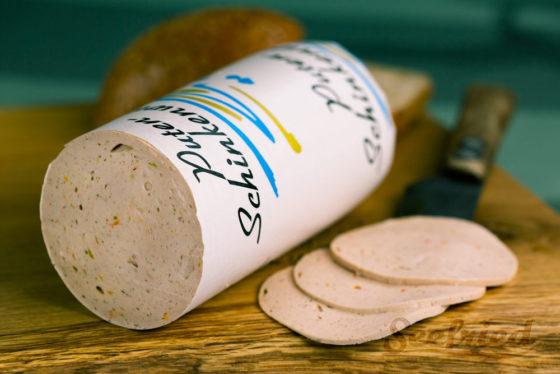 Putenschinkenwurst aufgeschnitten auf Holzbrett